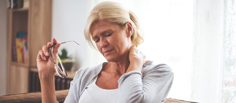middle aged woman holding her glasses while having a neck pain