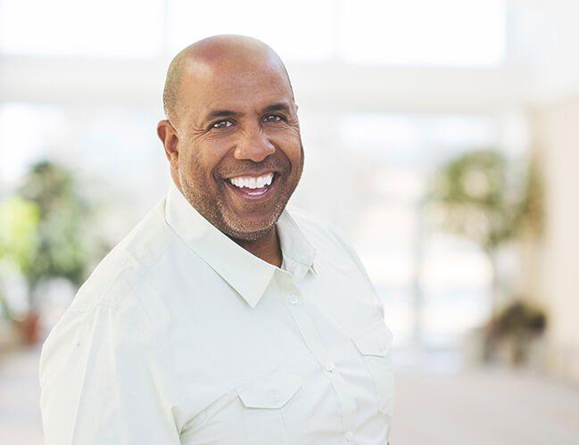 A smiling man wearing white long sleeve