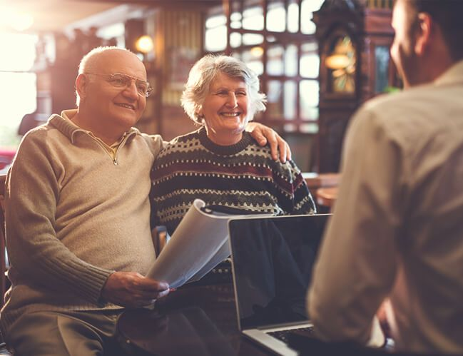 An elderly couple happy talking with man.