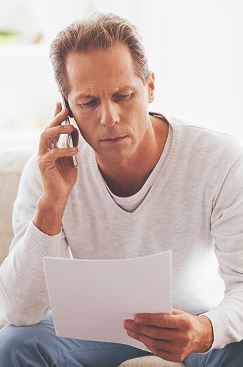 middle aged man looking at the document while calling