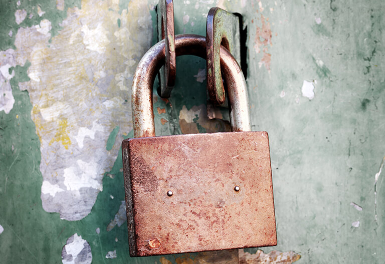 A rusted metal padlock fastening an iron bar.