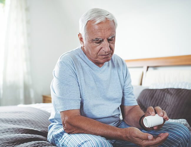 An elderly man sitting on a bed holding a bottle of medicine on his hand.