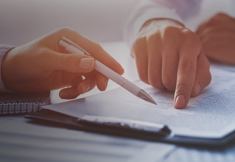 A finger pointing on a document and a hand holding a pen.
