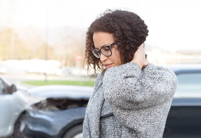 A woman feeling bad, holding her neck after having a car crash